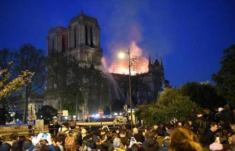 Crowds look on as flames and smoke billow from the roof at Notre Dame Cathedral in Paris on April 15, 2019. - A fire broke out at the landmark Notre Dame Cathedral in central Paris, potentially involving renovation works being carried out at the site, the fire service said.Images posted on social media showed flames and huge clouds of smoke billowing above the roof of the gothic cathedral, the most visited historic monument in Europe. (Photo by ERIC FEFERBERG / AFP)ERIC FEFERBERG/AFP/Getty Images