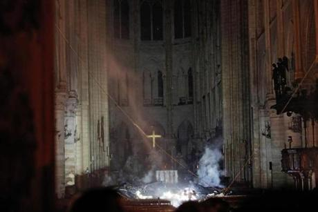 Smoke rises in front of the altar cross at Notre-Dame Cathedral in Paris on April 15, 2019, after a fire engulfed the building. - A fire broke out at the landmark Notre-Dame Cathedral in central Paris, potentially involving renovation works being carried out at the site, the fire service said.Images posted on social media showed flames and huge clouds of smoke billowing above the roof of the gothic cathedral, the most visited historic monument in Europe. (Photo by PHILIPPE WOJAZER / POOL / AFP)PHILIPPE WOJAZER/AFP/Getty Images