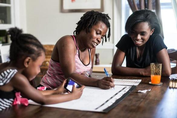 06/18/2016 ROSLINDALE, MA L-R Ammattieia Pierre (cq), 4, Sandy Guerrier (cq), and Amurah Pierre (cq) 15, go over their monthly chore chart at their home in Roslindale. (Aram Boghosian for The Boston Globe)