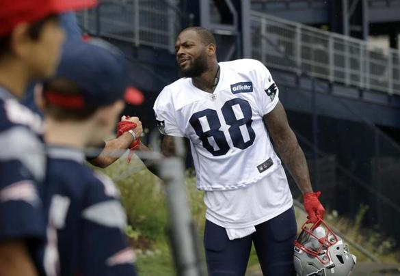 New England Patriots tight end Martellus Bennett greets fans as he steps onto the field before an NFL football training camp practice Sunday, July 31, 2016, in Foxborough, Mass. (AP Photo/Steven Senne)