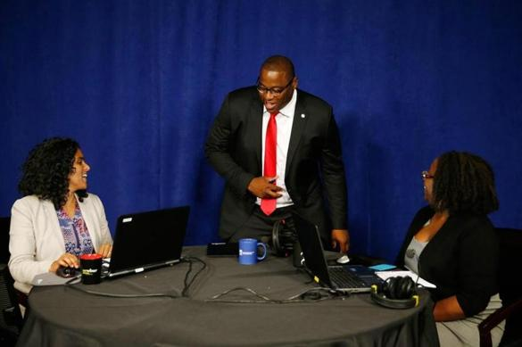 Boston Mayoral candidate Tito Jackson arrives to an interview by Radio Boston host Meghna Chakrabarti (L) and Meghan Iron, chief of the Boston Globe's City Hall Bureau.