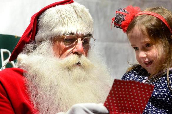 Hingham 12/01/2017: Bob Beal aka Santa from Hingham, reads Marielle Hoppe , 5 , from Hingham's Christmas list during her visit during the annual Christmas in the Square celebration in Hingham. Photo by Debee Tlumacki for the Boston Globe (south)