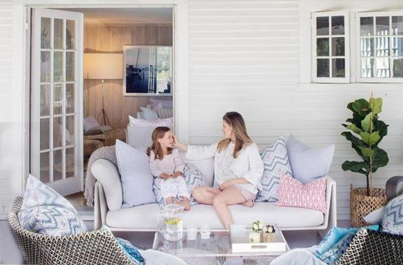 Homeowner and designer Amanda Pratt and her youngest daughter, Lily, relax on the screened porch off the living room.