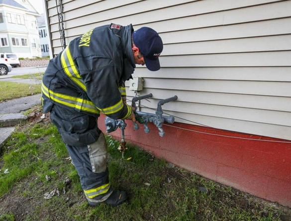Mandatory Credit: Photo by CJ GUNTHER/EPA-EFE/REX/Shutterstock (9881657g) A Salsbury Fire Department fireman turns off gas to a house in Lawrence, Massachusetts, USA, 13 September 2018. A series of reported gas explosions in towns north of Boston Massachusetts have set at least 39 homes ablaze and forced mandatory evacuation for residents. Gas explosions and fires erupt in Massachusetts, Lawrence, USA - 13 Sep 2018