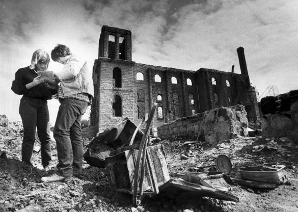 Lori Dybowski (left), a resident of the apartment building across the street from the 90-year-old Fall River Notre Dame Church that was destroyed by a fire, looked through a jewelry case found by her neighbor, Jeff McCallister, while digging for belongings on May 15, 1982. Dybowski and her family were left homeless by the fire.