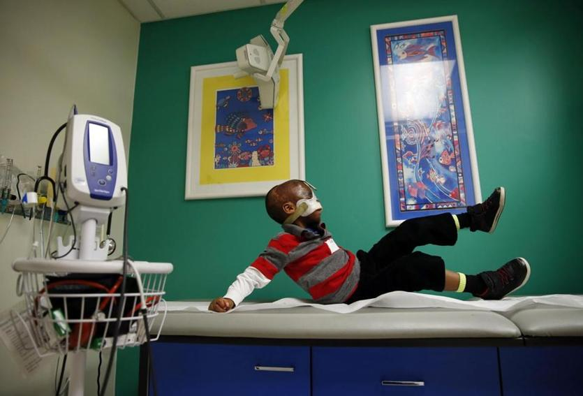 Boston, Massachusetts -- 3/10/2015-- Leo playfully climbs onto the exam table during a medical check up at Shriner's Hospital in Boston, Massachusetts March 10, 2015. Jessica Rinaldi/Globe Staff Topic: 042615burn Reporter: