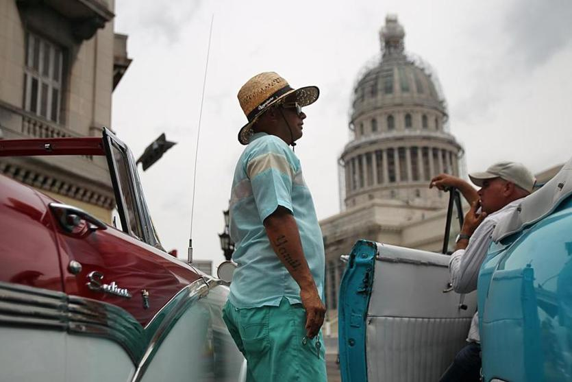 Havana, Cuba, 06/015/15, Taxi drivers with their restored antique cars wait for tourists in front of the Capitol building. Suzanne Kreiter/The Boston Globe