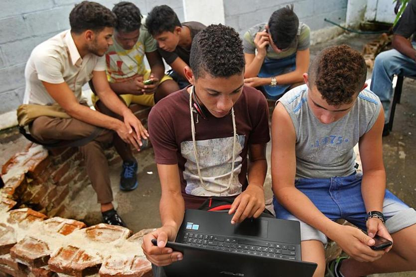 Havana, Cuba, 06/09/15, A rare source of free Wi-Fi provided by Cuban artist Kcho at his art/cultural center. Young people hover over laptops and phones under hot tin roof to have access to the internet. Suzanne Kreiter/The Boston Globe