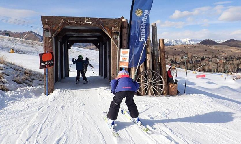 Kids shoot through a small tunnel on Dollar Mountain at Sun Valley Resort, which has a new Terrain That Teaches program for helping beginner skiers progress quickly.
