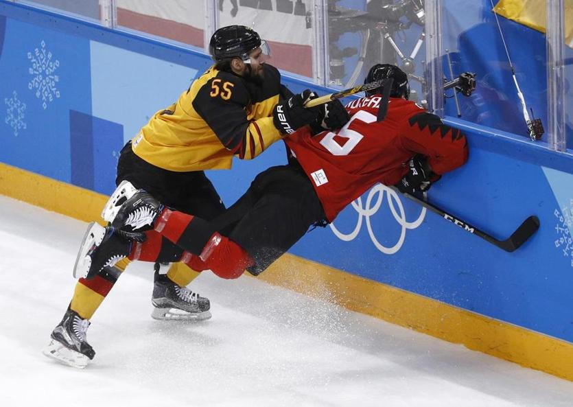 Germany's Felix Schutz sends Maxim Noreau of Canada face-first into the boards.