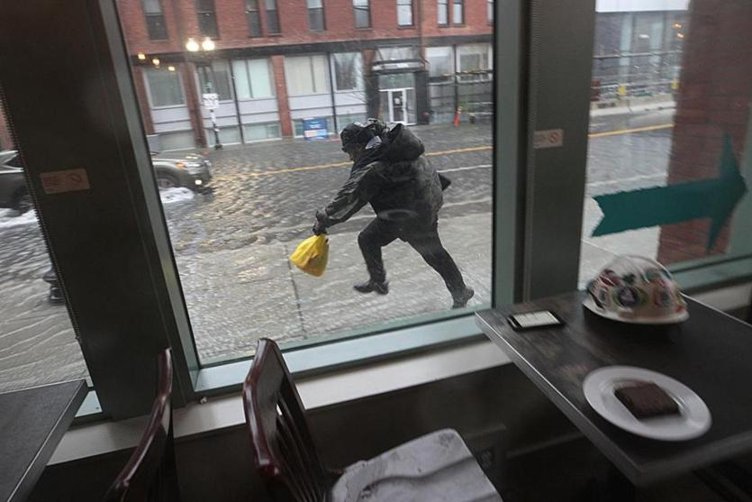 A person dashed through the rising water as seen from inside a dry coffee shop.