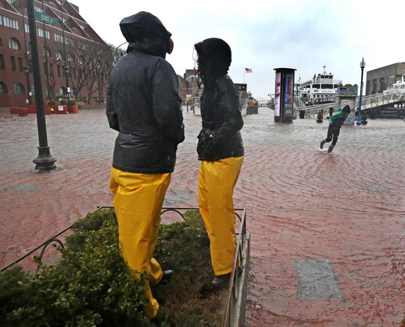 A couple kept high and dry by standing on top of a garden planter on State Street.