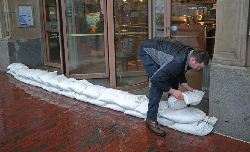 Ryan Adams placed sandbags at the entrance of 255 State St. in Boston.