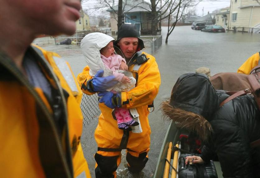 A rescue worker held a crying baby rescued with her mother from a flooded home on Post Island Road in Qunicy.