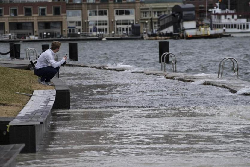 Boston, MA - 3/3/2018 - A man watches as waves crash into Fan Pier along the Seaport district in Boston, MA, Mar. 3, 2018. The enormous nor'easter that brought flooding, damaging winds, and even heavy snow to parts of New England has now pushed farther out to sea. Although the storm is farther away, its influence will be felt for a couple of days. with winds and potential flooding expected. (Keith Bedford/Globe Staff)