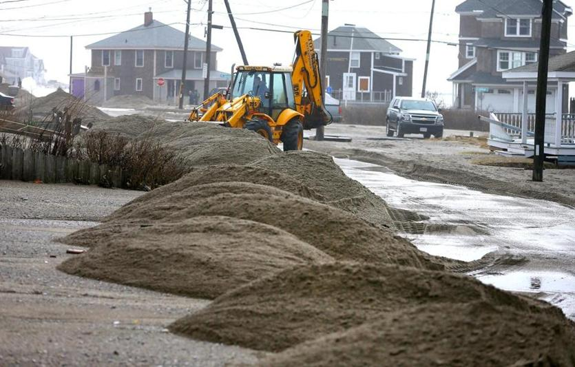 Scituate-03/03/18-Scituate storm aftermath. People came out to view the flooding and damage to Scituate at Cedar Point and near the ocean. A front end loader clears Turner Road which was covered with sand.John Tlumacki/Globe Staff(metro)