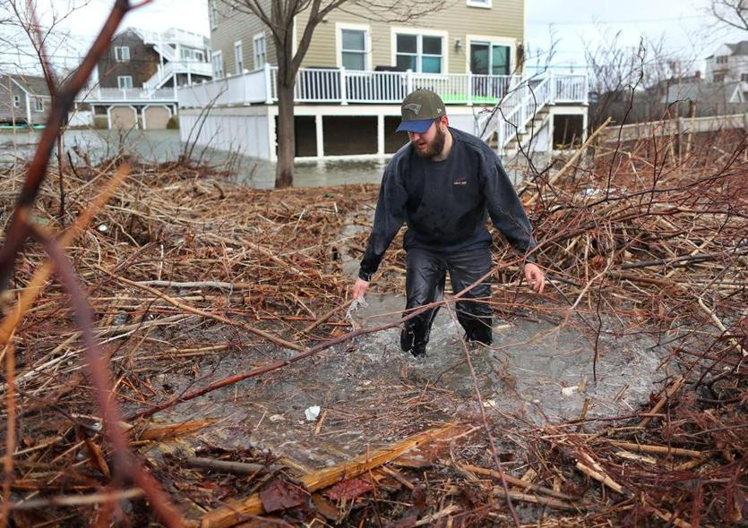 Scituate-03/03/18-Scituate storm aftermath. People came out to view the flooding and damage to Scituate at Cedar Point and near the ocean.Jacob Gurner walks through a flood backyard after checking on his home on Otis Road. John Tlumacki/Globe Staff(metro)
