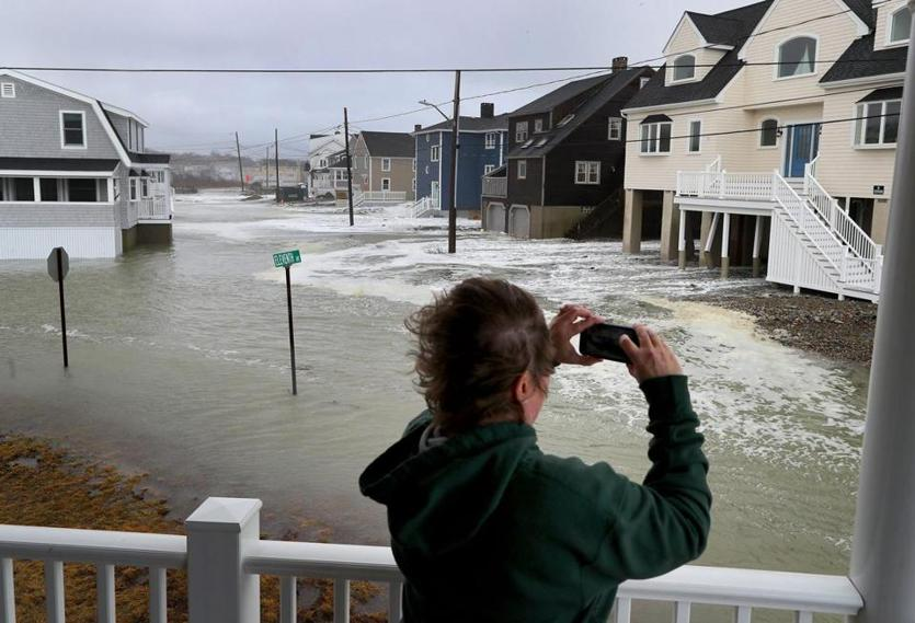 Scituate-03/03/18-Scituate storm aftermath. People came out to view the flooding and damage to Scituate at Cedar Point and near the ocean. Sue Parmer(cq) takes photos of the rising surf on Oceanside Drive at high tide. John Tlumacki/Globe Staff(metro)