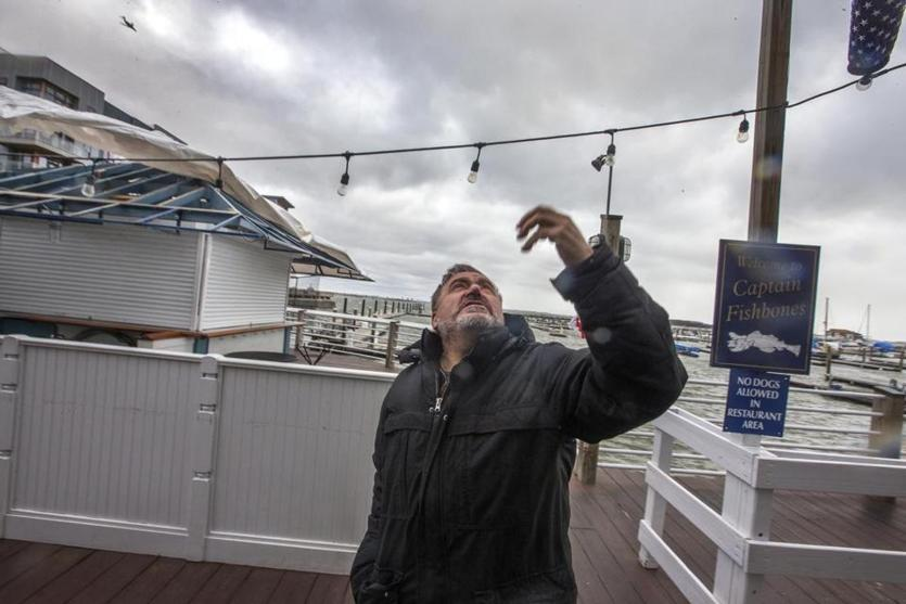 Quincy, Ma-March 2, 2018-Stan Grossfeld/Boston Globe---Loid 8.4.1159877283- Donato Frattaroli, owner of Captain Fishbones in Marina Bay cleans up after storm.