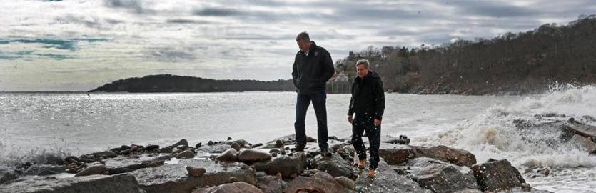 Gloucester, MA 3/4/2018: Massachusetts Governor Charlie Baker (left) came to Gloucester today to inspect some of the areas that were affected by the weekend storm. He is pictured walking on a sea wall at Stage Fort Park with State Senator Bruce Tarr (R-Gloucester, right) where moments earlier they had gotten wet from a wave crashing onto them. (Jim Davis/Globe Staff)