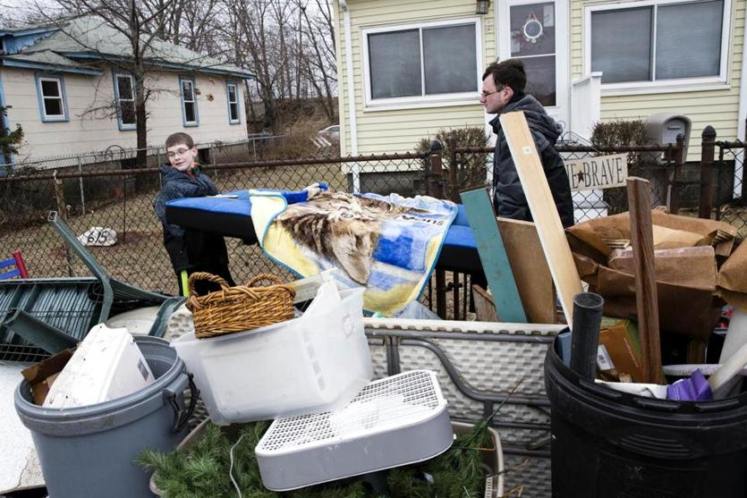 Walter (left) and Ben Bardon piled flood-damaged belongings outside of their family's Quincy home on Monday.