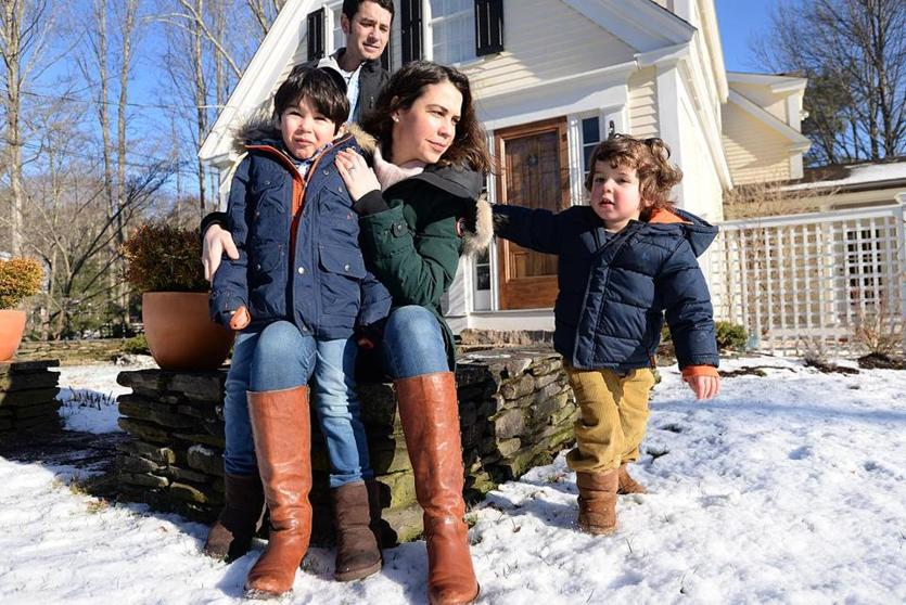 Allicyn Aubut and her husband, Chris, with their children, Miles, 5, and Flecher, 3, in front of their Elm Street home in Duxbury.