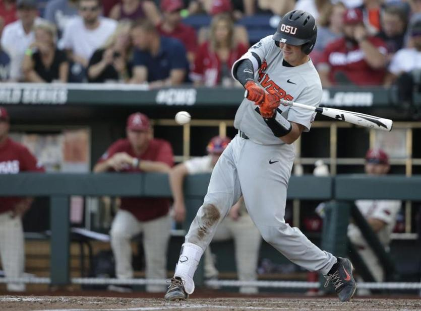 Oregon State's Adley Rutschman hits an RBI single to score Cadyn Grenier during the third inning. Rutschman was the CWS Most Outstanding Player, setting a series record with 17 hits.