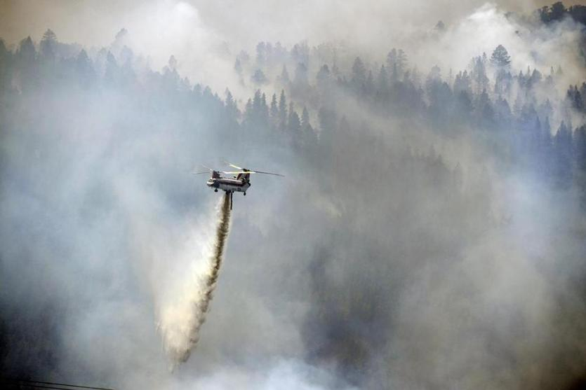 A Chinook helicopter makes a water drop near Paradise Acres as the aerial assault continues to help put out a wildfire on La Veta Pass, Sunday, July 8, 2018, near La Veta, Colo. (Helen H. Richardson/The Denver Post via AP)