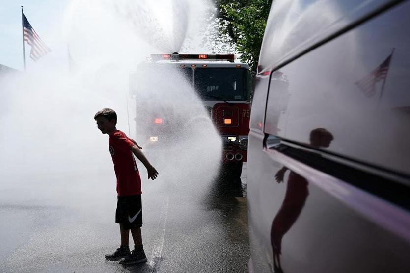 WASHINGTON, DC - JULY 04: A boy cools himself down in water spray from a fire truck outside the annual Smithsonian Folklife Festival on Independence Day July 4, 2018 in Washington, DC. An oppressive heat has settled over much of the nation and is expected to last at least through the end of the week, according to forecasts. (Photo by Alex Wong/Getty Images)