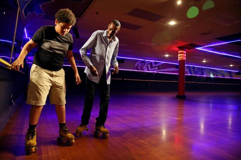 Boston, MA - August 09, 2018: Zach Durham, 14, gets a skating lesson from Edward Warren at Chez-vous Roller Rink in the Dorchester neighborhood of Boston, MA on August 09, 2018. Warren had invited friends to celebrate his 38th birthday at the rink that he's been skating at since he was 10. This was Durham's first time on skates. The rink has been in operation for 85 years. (Craig F. Walker/Globe Staff) section: metro reporter: