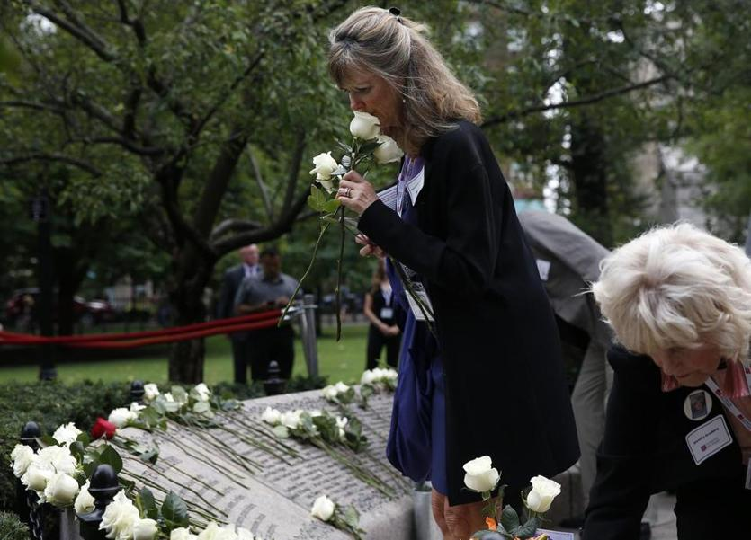 Boston, MA--9/11/2018-- A family member whose loved one was killed in the September 11th attacks lays flowers during a 9/11 wreath laying ceremony at Boston Public Garden. (Jessica Rinaldi/Globe Staff) Topic: 12nineeleven Reporter: