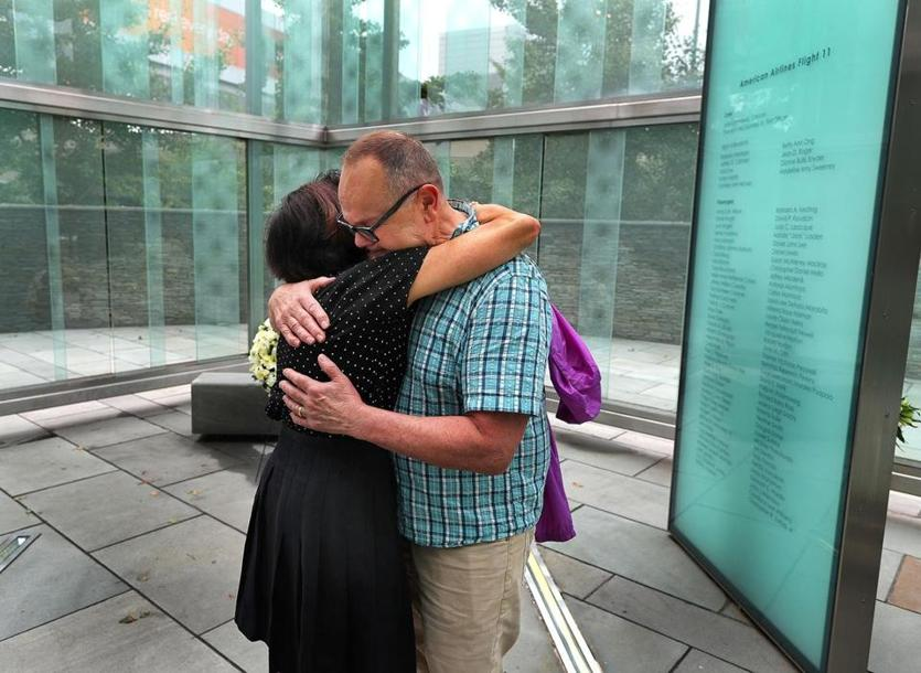 Boston -09/11/18-An emotional John Krajovic is hugged by Joni Belfiore inside the Logan Airport 911 Memorial. Krajovic was the Massport Project Director for the memorial, and Belfiore is an employee of Massport. Belfiore worked with the families to get their input on the design. The glass memorial has the names etched of passengers and crew of United Flight 175 and American Airlines Flight 11, both which took off from Logan on September 11, 2001 and crashed into the World Trade Center in New York. Photo by John Tlumacki/Globe Staff(metro)