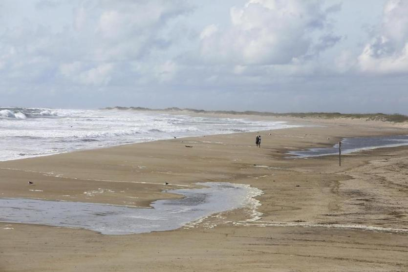 Surf rolled in near Cape Point on Hatteras Island, N.C., while a couple of people who stayed behind drank it all in.