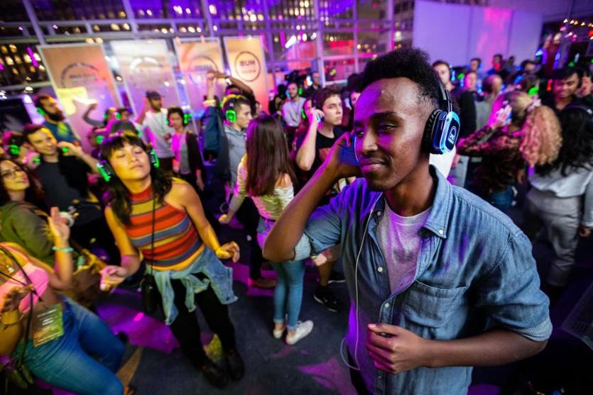 Brandon Washington, 32, of Cambridge listened to music on wireless headphones during the Silent Disco bash at City Hall Plaza on Thursday night.