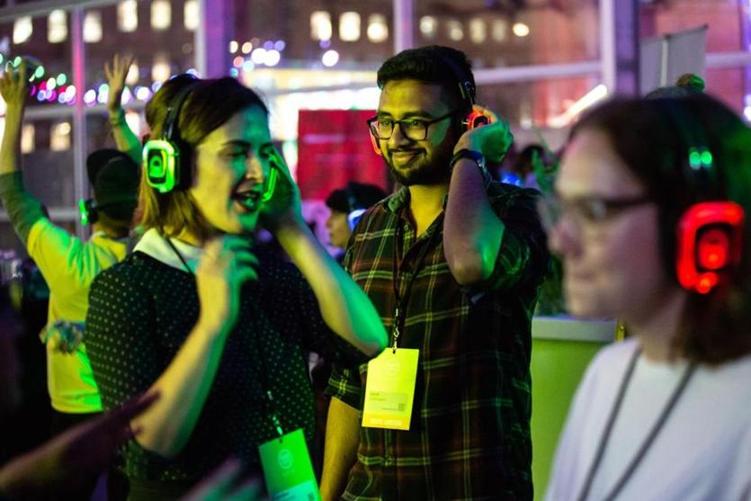 Lonai Sunny, 27 (center), danced with Shallon Silvestrone, 30 (left), while listening to music on wireless headphones at the Silent Disco at HUBweek on Thursday.