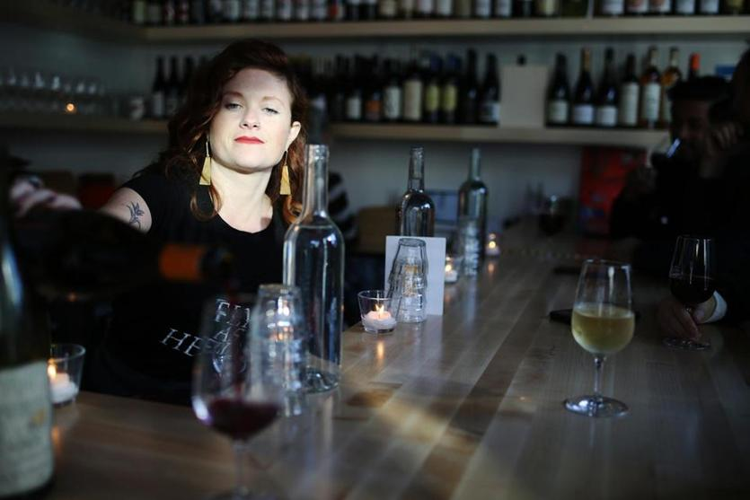 Lauren Friel, owner of Rebel Rebel, pours a glass of wine at the bar.