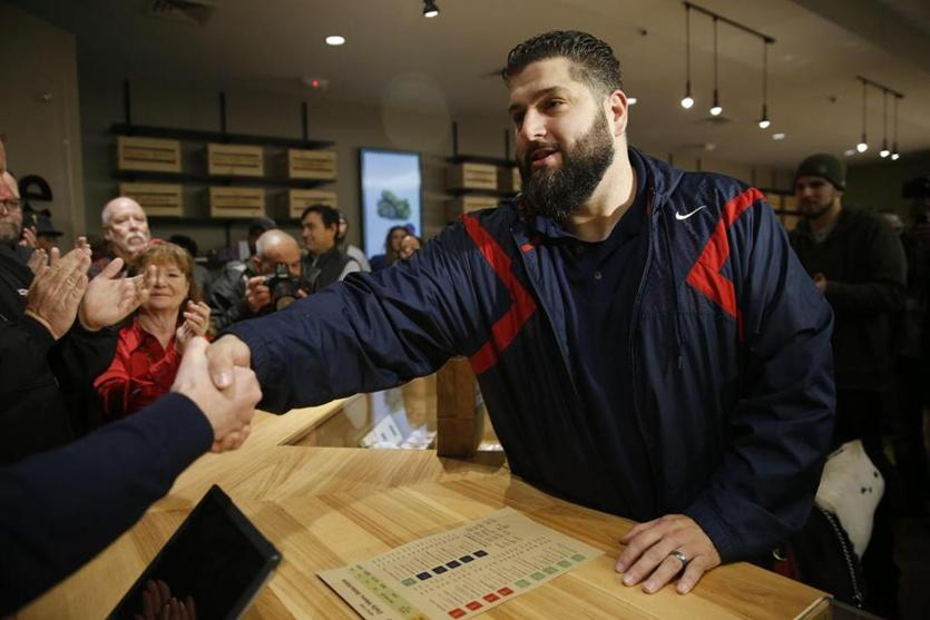 Leicester, MA, 11/19/2018 -- Iraq Veteran Stephen Mandile, of Uxbridge, shakes hands with Cultivate President Sam Barber as he makes the first purchase at the opening of Cultivate, one of the state's first two pot shops. This the first day the store can sell recreational marijuana to adults 21 and older. (Jessica Rinaldi/Globe Staff) Topic: 21potopen Reporter: