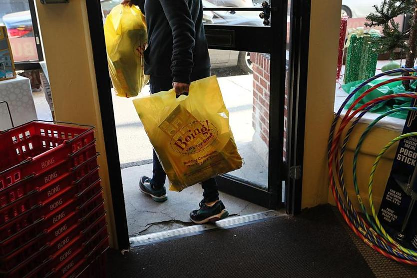 "Jamaica Plain, MA., 12/12/2018, A customer leaves Boing toy store with holiday gifts. Amid the downfall of Toys ""R"" Us and the mindbending growth of Amazon, the toy retail scene is morphing before our very eyes. The local toy shop Boing in JP is offering home delivery and curbside pickup to compete with Amazon. Suzanne Kreiter/Globe staff"