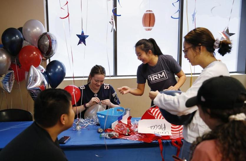 Boston, MA, 02/3/2019 -- Volunteers from Northeastern including Heather Guglietti (2nd from L) and Sydny Poh(cq) (3rd from L) hung balloons for a tailgate party at St. Francis House ahead of the Super Bowl. (Jessica Rinaldi/Globe Staff) Topic: 04stfrancisparty Reporter: