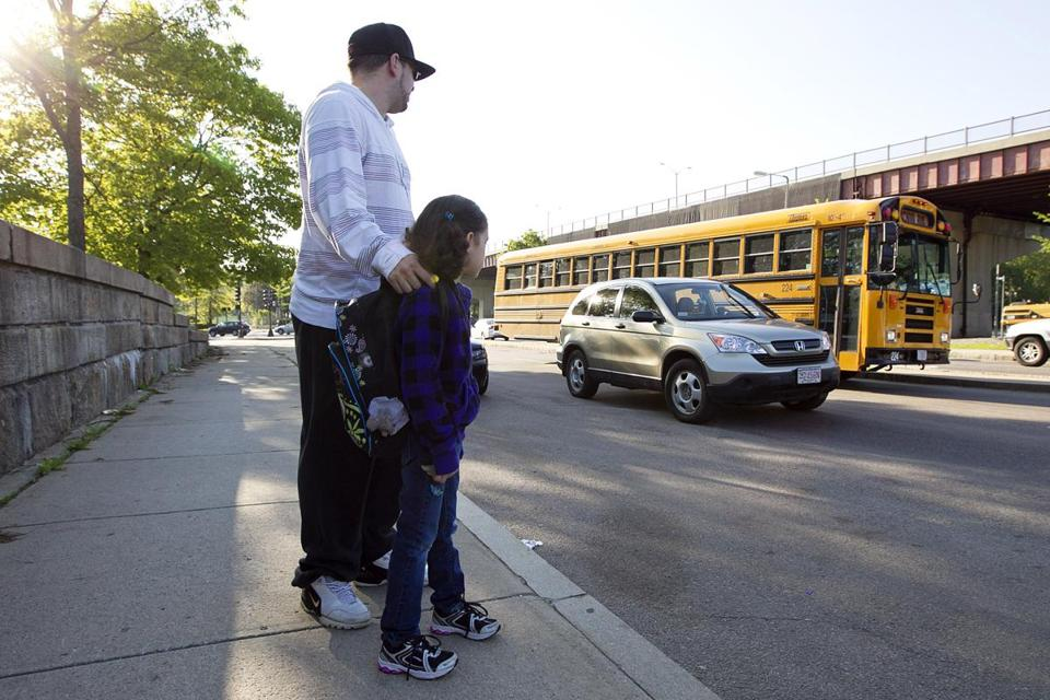 Alex Saavedra waits with his daughter Aryana, 7, as her bus to Fiske Elementary School in Wellesley pulls up at the Forest Hills MBTAstation in Roslindale.