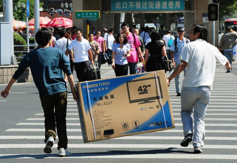 Chinese shoppers carried a flat screen television along a road in Beijing in September.