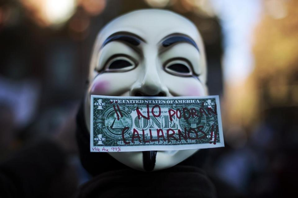 "A protester wearing a Guy Fawkes mask, symbolic of the hacktivist group ""Anonymous"", is pictured with a fake dollar bill as he takes part in a march called by the Spanish ""indignant"" movement against politicians, banks, the economic crisis and high unemployment in Madrid November 27, 2011. The words on the bill read, ""We won't be silenced"". REUTERS/Susana Vera (SPAIN - Tags: CIVIL UNREST POLITICS BUSINESS TPX IMAGES OF THE DAY)"