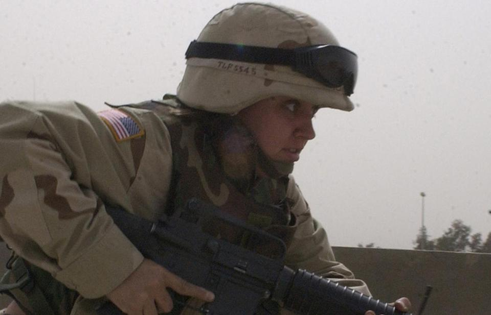 "Army Spec. Theresa Lynn Flannery runs for cover as the Spanish base comes under attack outside Kufa, Iraq, near Najaf, in this April 4 2004, file photo. Along with a Bronze Star with a ""V"" for valor recommendation, Flannery, 26, from Kentucky, is also receiving a Purple Heart for an injury she received while under fire during a battle at Najaf, Iraq. (AP Photo/Gervasio Sanchez, File)"