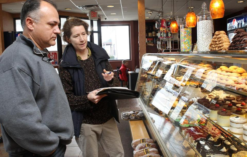 Joseph Torretta, owner of D'Amici's Bakery in Lynn, describes to Didi Emmons the ingredients he uses in products in his display case. Emmons was hired by Lynn officials to help restaurant and bakery owners comply with the city's ban on trans fats.