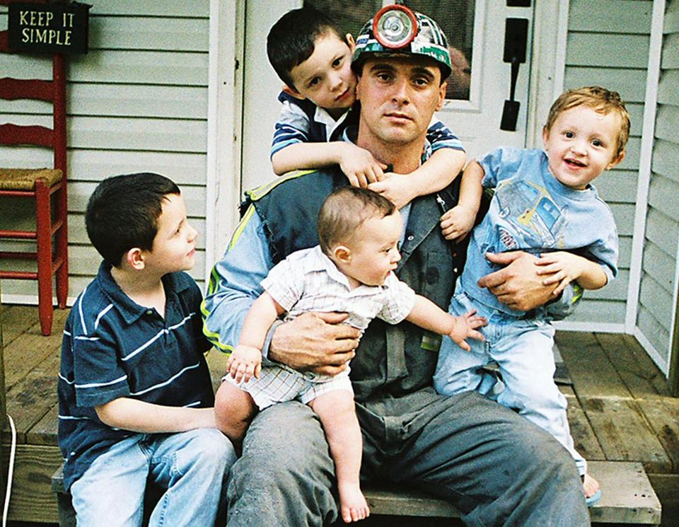 Miner Allen Turner sits on his porch with his four children in Cawood, Ky.