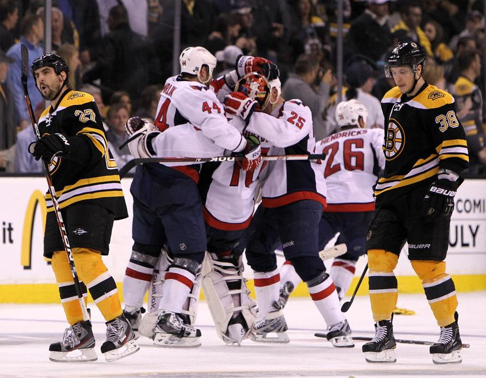 Capitals rookie goaltender Braden Holtby was engulfed (center) as the Capitals celebrated their Game 7 overtime victory, much to the dismay of Bruins Mike Mottau (27) and Jordan Caron.