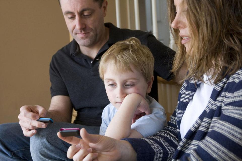 Jackson Horman, 5, at home in Beverly with parents Stacey Malay and Jason Horman, who count steps on their FitBit activity trackers.