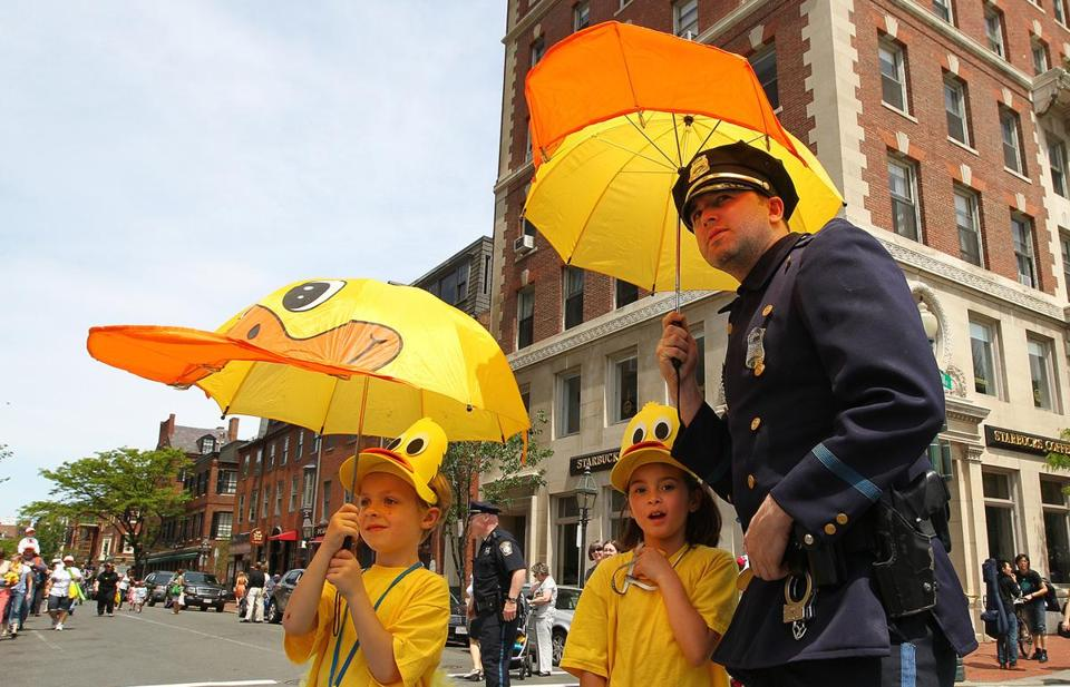 JUST DUCKY: Jacob Hardy and Tea Robinson of Hyannis with Robert Flynn (as Officer Michael) at the Duckling Day parade on Beacon Hill, Charles Street on May 13.