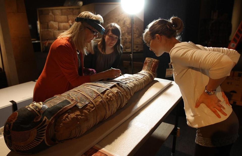 Mimi Leveque, Peabody Essex Museum conservator; Becca Melius curator at Boston's Museum of Science; and Rebecca Barber, an intern, examined a mummy.