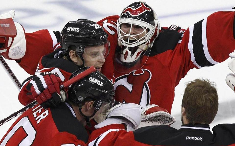 Devils goalie Martin Brodeur (top) celebrates with teammates as New Jersey  ousted the Rangers 9973afc9c